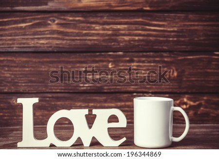 White cup and wooden word Love on table. - stock photo