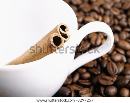 white cup, coffee beans and cinnamon sticks