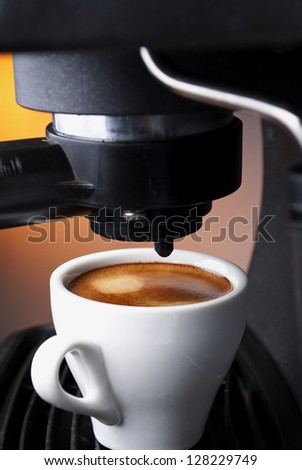 white cup filled with coffee in the coffee machine - stock photo