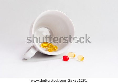 White cup filled with red and yellow medicine pills and capsules, isolated on white background. - stock photo