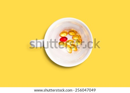 White cup filled with red and yellow medicine pills and capsules  isolated on yellow background. - stock photo