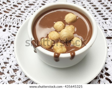 White cup for your text. Milk chocolate. Liquid milk chocolate. Chocolate with hazelnuts.  - stock photo