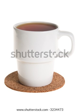 White cup full of tea on a cork pad taken from side isolated on white - stock photo