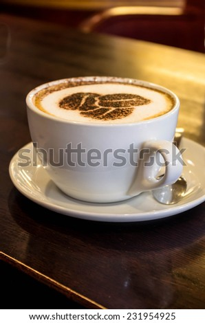 White cup of aromatic coffee, very nicely decorated chocolate - stock photo