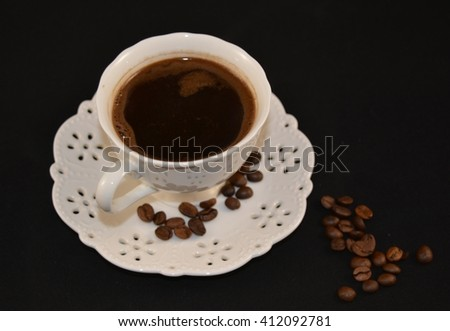 White cup of black coffee and grain of coffee. Black background.