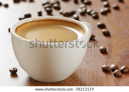 White cup of coffee and coffee beans on wooden surface.