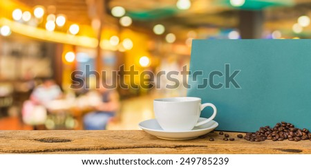White cup of coffee and green chalkboard menu on wooden bar with blurred image of shopping mall and people . - stock photo
