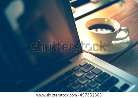 white Cup of coffee and laptop on wooden table. business concept - stock photo