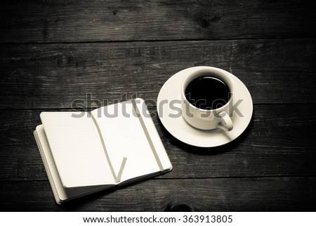 White cup of coffee and notebook on old wooden table. Toned.