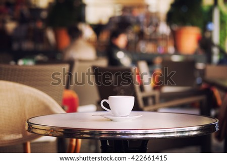 White cup of coffee at the summer cafe table - stock photo