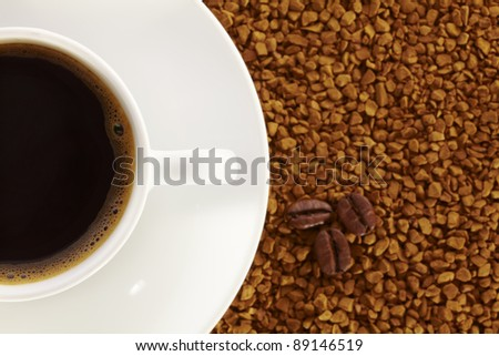 White cup of coffee on the back of instant coffee and three coffee beans. - stock photo