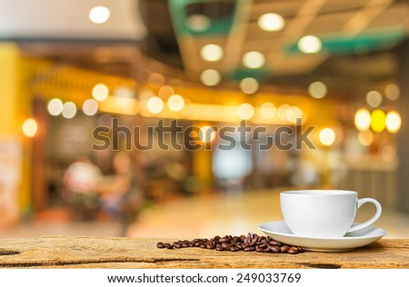 white cup of coffee on wooden bar  in Coffee shop blur background with bokeh image . - stock photo