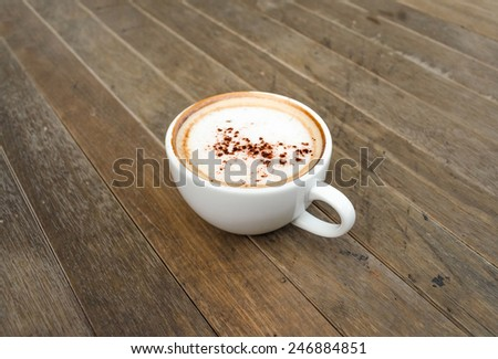 White cup of coffee on wooden table. - stock photo