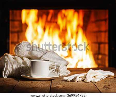 White cup of coffee or tea, woolen scarf, gloves and cap on wooden table near  fireplace. Winter and Christmas holiday concept