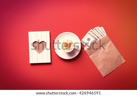 white cup of coffee, postcard and money on the red background - stock photo
