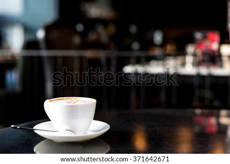 white cup of coffee, ready for branding, on the cafe table - stock photo