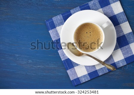 White cup of coffee with checkered napkin on blue wooden table. Top view point. - stock photo