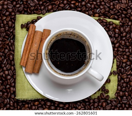 white cup of coffee with cinnamon sticks. View from above. - stock photo