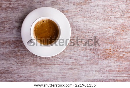 white cup of coffee with foam on saucer with place for your text, top view - stock photo