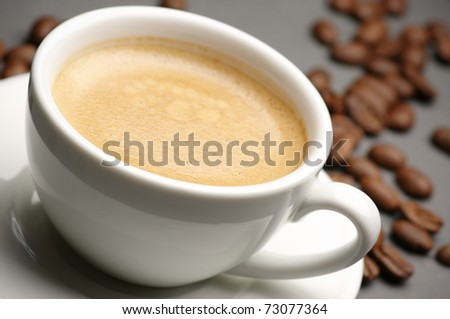 White cup of coffee with froth and coffee beans on dark gray background. - stock photo