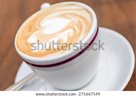 White Cup Of Coffee With Heart Pattern On Wooden Table - stock photo