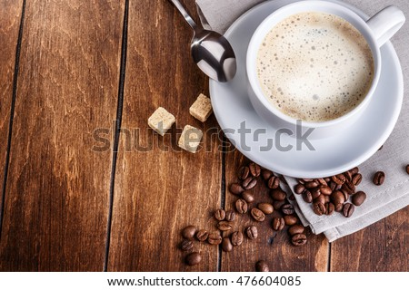 white cup of coffee with roasted beans refined sugar napkin