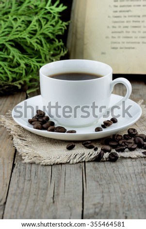 White cup of coffee with roasted coffee beans old book and thuja branches on wooden background - stock photo