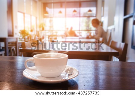 White cup of coffee with smoke on table in cafe. warm tone.