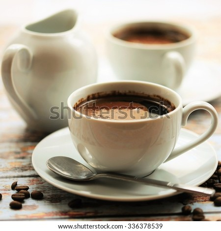 white cup of coffee with spoon , milk jar and coffee beans on wood background. - stock photo