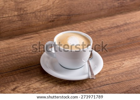 White cup of delicious aromatic freshly prepared cappuccino with generous portion of soft cream on a rustic wooden table. - stock photo