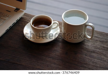 White cup of espresso and white cup of hot water on wooden desk.