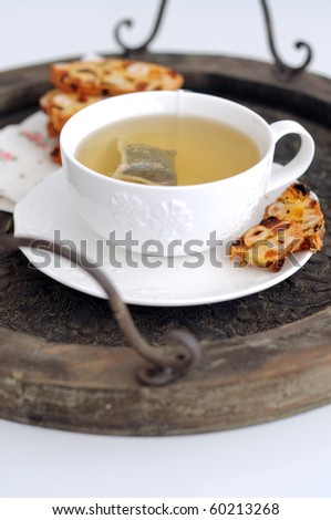 White cup of  green tea and biscotti on wooden tray - stock photo