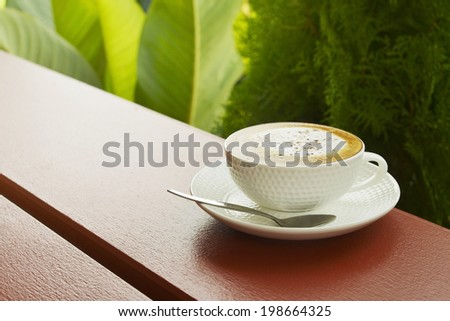white cup of hot cappuccino coffee in terrace  - stock photo
