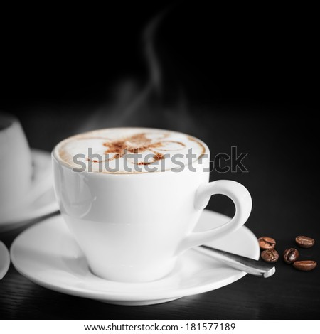 White cup of hot cappuccino on black background - stock photo