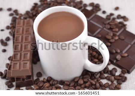 White cup of hot chocolate on coffee beans and chocolate background  - stock photo