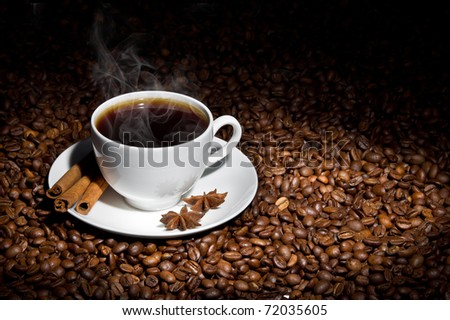 White cup of hot coffee on coffee beans with three sticks of cinnamon and star anise fruits. Partial lighting