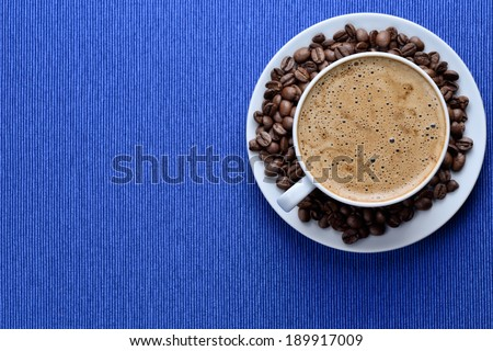 White cup of hot coffee on dark blue canvas - stock photo