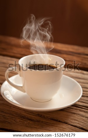 White cup of hot coffee on wood background - stock photo