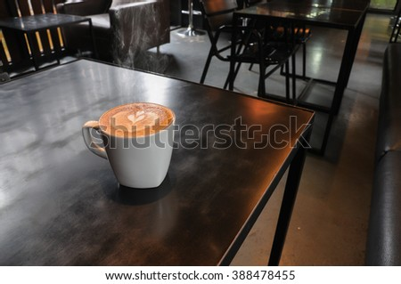 white cup of hot coffee on wooden table in coffee shop - stock photo