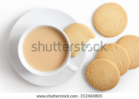 White cup of tea and saucer with shortbread biscuits from above. - stock photo
