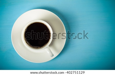 White cup of tea on blue wooden table. Toned. - stock photo