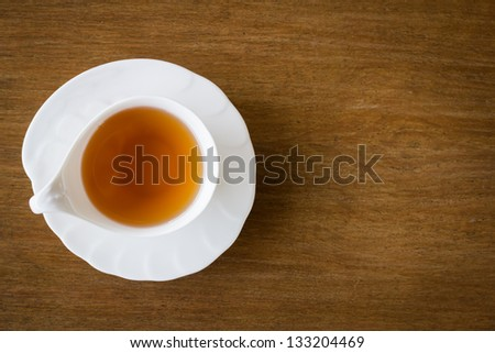 White cup of tea on wood background, top view - stock photo