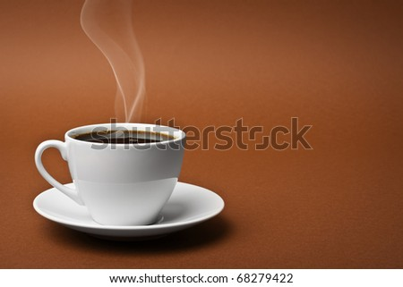 White cup on a saucer filled with coffee - stock photo