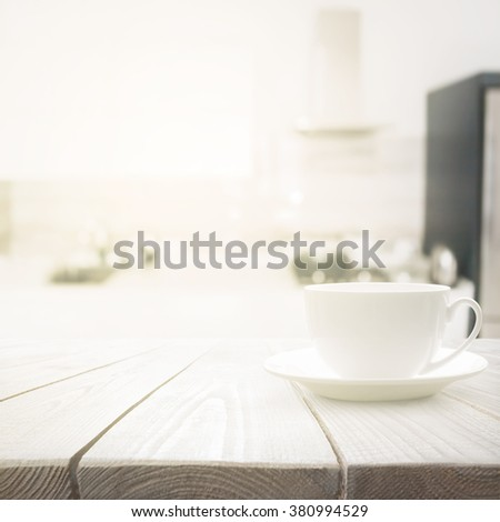 White cup on wooden table over blured kitchen interior background - stock photo