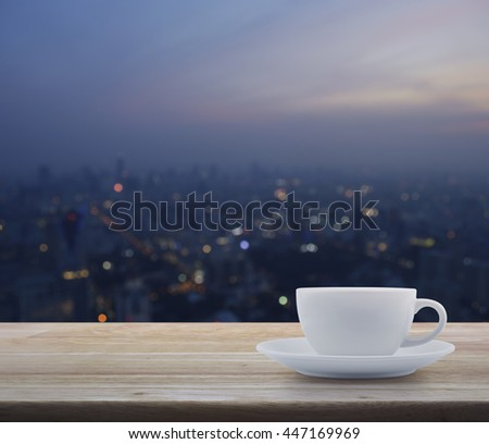 White cup on wooden with blurred aerial view of cityscape on warm light sundown