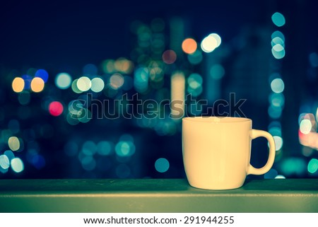 White cup over city night bokeh background - Vintage effect style - stock photo
