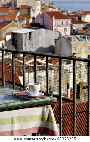 White cup over table at cafe over Alfama quarter at Lisbon - stock photo