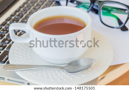 white cup tea&laptop on the wood table - stock photo