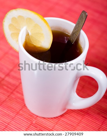 white cup with black tea and piece of lemon