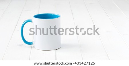 white cup with blue handle and inside on wooden surface - stock photo